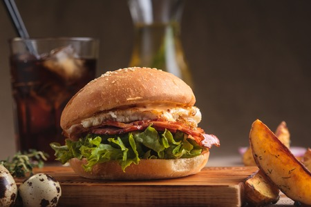 gluttony: Concept: restaurant menus, healthy eating, homemade, gourmands, gluttony. Trendy breakfast burger with ham and eggs with ingredients, drinks and potato wedges on messy vintage wooden background.