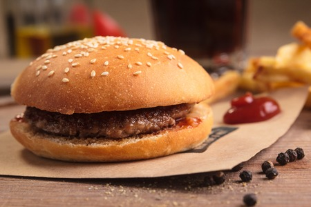 Concept: restaurant menus, healthy eating, homemade, gourmands, gluttony. Classic hamburger with ingredients, drinks and french fries on messy vintage wooden background.