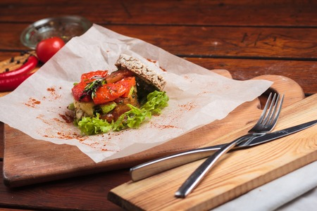 gluttony: Concept: restaurant menus, healthy eating, homemade, gourmands, gluttony. Vegetable salad served on paper on weathered wooden table.
