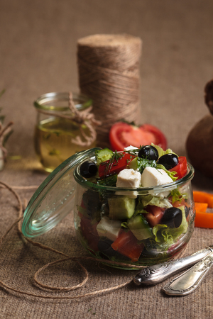 gluttony: Concept: restaurant menus, healthy eating, homemade, gourmands, gluttony. Greek salad served in glass jar with ingredients on weathered sackcloth background. Stock Photo