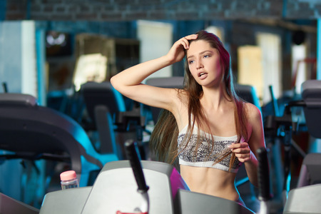 Concept: power, strength, healthy lifestyle, sport. Beautiful attractive feminine sensual girl run during fitness workout at the gym.
