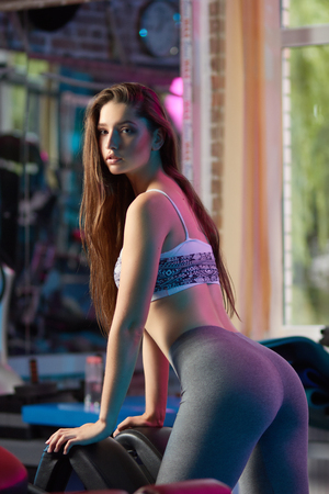 Concept: power, strength, healthy lifestyle, sport. Beautiful attractive feminine sensual girl doing fitness workout at the gym.