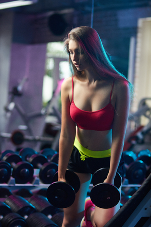 Concept: power, strength, healthy lifestyle, sport. Beautiful attractive feminine sensual girl doing fitness workout with dumbbells at the gym. Standard-Bild