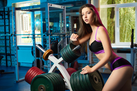 Concept: power, strength, healthy lifestyle, sport. Beautiful attractive feminine sensual girl take breath during fitness workout at the gym.
