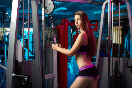 Concept: power, strength, healthy lifestyle, sport. Beautiful attractive feminine sensual girl doing fitness workout with cable machine at the gym.