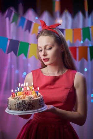 Concept: celebration, birthday. Beautiful young vintage pin up style girl standing in colorful lighted scene holding cake with candles.
