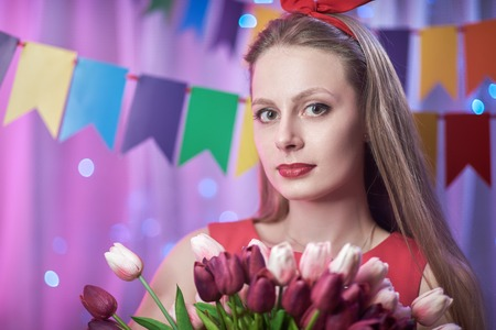 Concept: celebration, birthday. Beautiful young vintage pin up style girl standing in colorful lighted scene holding flowers. Standard-Bild