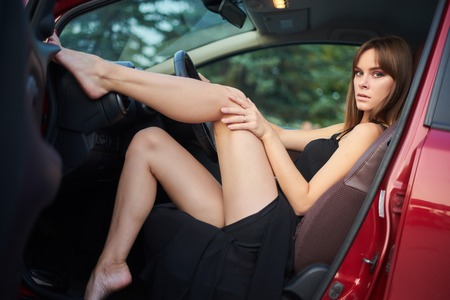 Concept: strong independent young woman in car. Beautiful serious girl sit behind the wheel in a sensual pose at twilight with open door and legs up. Standard-Bild