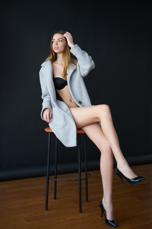 Concept: professional fashion lifestyle. Beautiful model posing in studio during classic test shooting wearing black lingerie and light blue coat. Woman show poses and emotions. Full-length portrait.