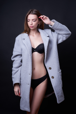 Concept: professional fashion lifestyle. Beautiful model posing in studio during classic test shooting wearing black lingerie and light blue coat. Woman show poses and emotions.