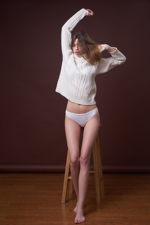 Concept: professional fashion lifestyle. Beautiful model posing in studio during classic test shooting wearing white sweater and white lingerie. Woman show poses and emotions. Full-length portrait. Imagens