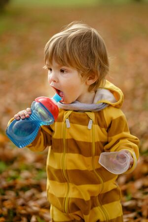 Concept: family, kids. Happy little child, baby boy with water bottle laughing and playing in the autumn on the nature walk outdoors at park