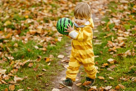 Concept: family, kids. Happy little child, baby boy laughing and playing with green ball in the autumn on the nature walk outdoors at park