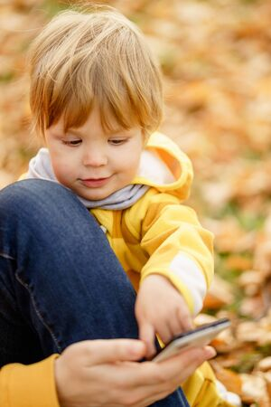 Concept: family, kids. Happy little child, baby boy laughing and playing with mothers smartphone in the autumn on the nature walk outdoors at park