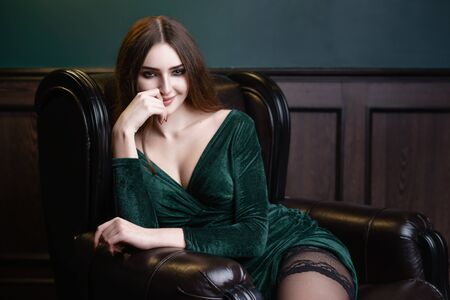 Concept: fashion, sensuality, tenderness, attraction. Beautiful woman with long hair sensual green dress and stockings studio photoshoot