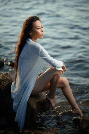 Concept: tourism, holidays, travel. Young lean pretty asian girl in two pieces green swimsuit and long white shirt relax on seashore at sunset. Fashion photoshoot.