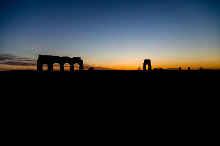 Sunset with silhouette of the park of Aqueducts in Rome (Italy) Archivio Fotografico