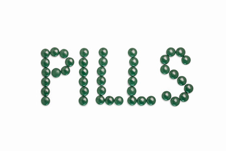 Pills written with green pills - white background