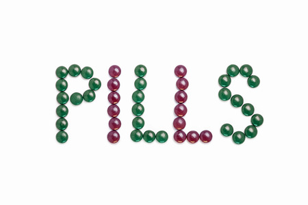 Pills written with green and purple pills  - white background