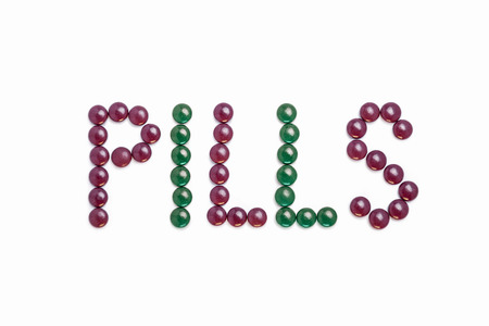 Pills written with purple and green pills  - white background