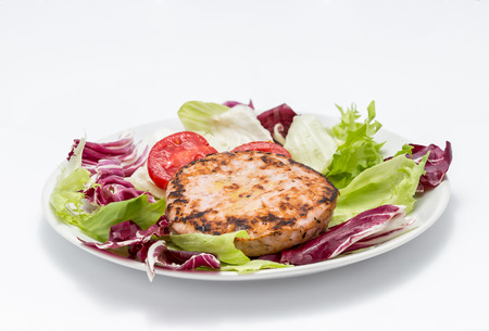 Chicken burger over salad - Two burgers, chicory, lettuce and tomato