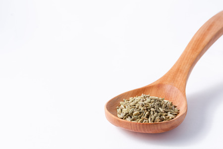 Fennel seeds in a wooden spoon spoon on the right Archivio Fotografico