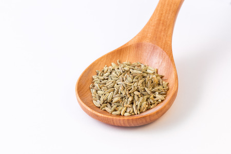 Fennel seeds in a wooden spoon view from top