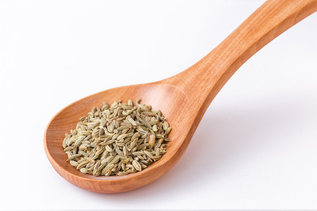 Fennel seeds in a wooden spoon. Spoon diagonally closeup on fennel