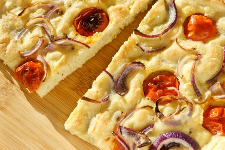 Focaccia with onion and tomato - two slices on center closeup