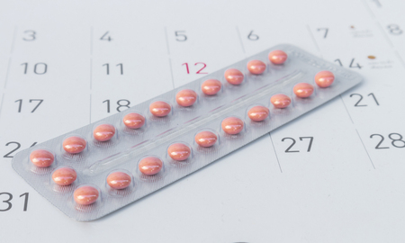 Close up birth-control pill with date of calendar background, health care and medicine concept Standard-Bild