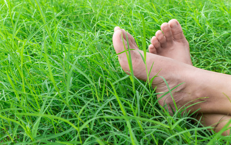 Woman bare feet on green grass, relax and holiday concept Stock Photo