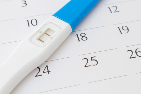 two people fertility: Pregnancy test on calendar background, health care concept