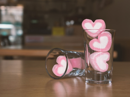 heartshaped: Marshmallow pink heart shape in glass on wood table background, vintage tone