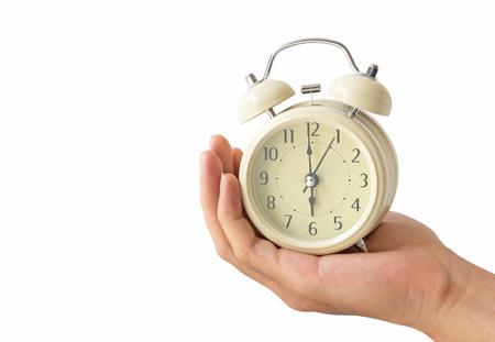 Hand holding retro alarm clock with white background