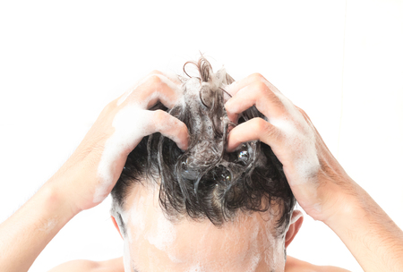 Closeup young man washing hair with white background, health care concept 版權商用圖片