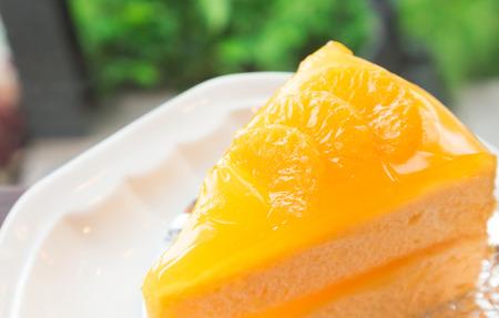 Closeup orange cake on wood table with nature background