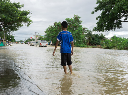 SAKON NAKHON, THAILAND - JULY 29, 2017 : Boy walking with water flooded Stock fotó - 85518860