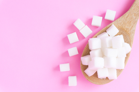 Closeup sugar cubes on wooden spoon with pink background, health care concept Stock Photo