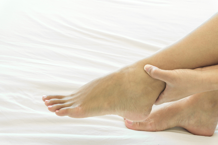 Woman hand holding ankle with pain on white bed, health care and medical concept