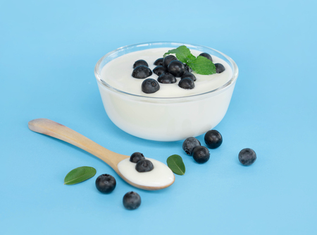 Close up yogurt with fresh blueberries fruit in glass bowl on blue background Stock Photo