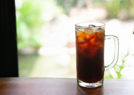Closeup glass of ice americano coffee with green nature background, selective focus