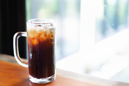 Closeup glass of ice americano coffee on wood table with green nature background, selective focus