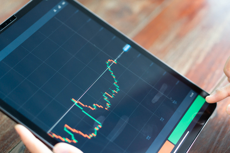 Closeup hand holding digital tablet computer with graph of Binary option for trading platform, setective focus