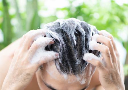 Closeup jonge man haar wassen met shampoo buiten, gezondheidszorg concept, selectieve aandacht