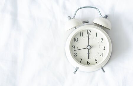 Close up alarm clock on white bed, selective focus
