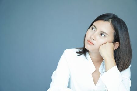 Woman thinking and looking something with blue background Banco de Imagens
