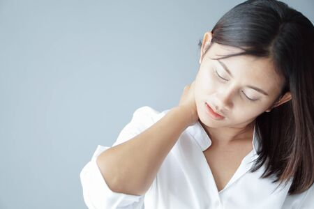 Closeup woman holding neck with pain after waking up on bed, healthy care and medical concept