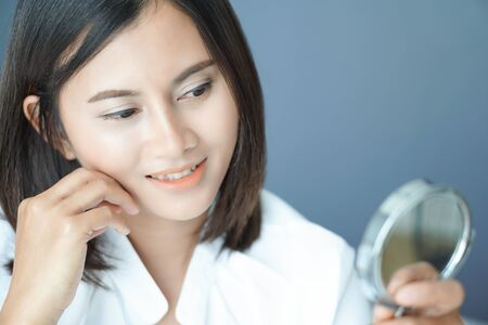 Close up face of woman looking the mirror with happy feeling, health care and beauty concept