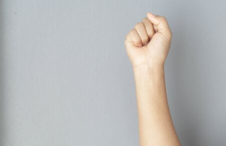 woman hand with clenched fist on grey background