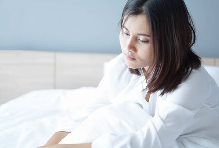 Closeup woman sitting on bed in the bedroom with depressed feeling, selective focus